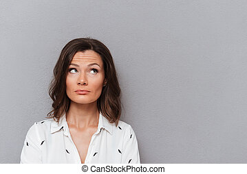 Pensive woman in shirt looking up