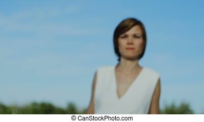 Pensive woman in white dress walking outdoor