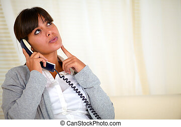 Pensive woman looking up speaking on phone