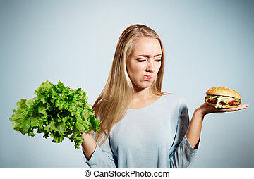 Pensive woman making decision between healthy food and fast food