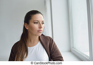 pensive woman near the window