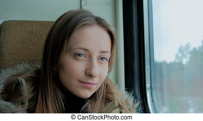 Pensive woman relaxing and looking out of a train window