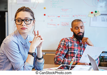 Pensive woman sitting and thinking while her male colleague reading