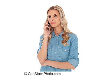 pensive woman speaking on  phone is looking up to side