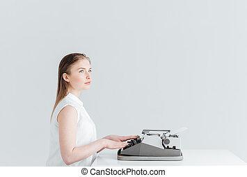 Pensive woman typing on retro machine