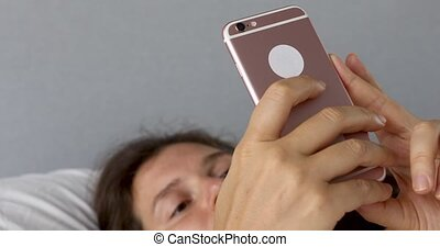 Pensive woman uses phone - Beautiful female use cell at home...