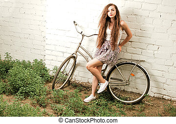 Pensive woman with city bike leaning back against white brick wall in summertime retro color shot