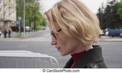 Pensive woman with sad face walking on urban street,...