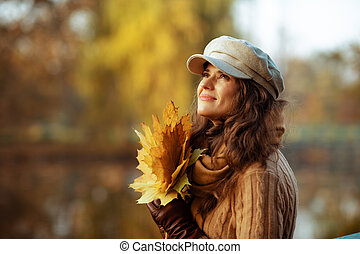 pensive woman with yellow leaves looking up at copy space