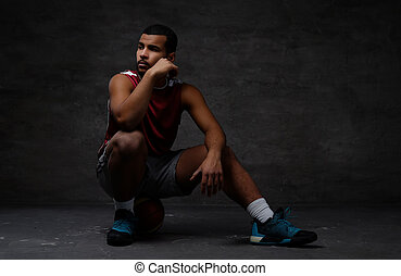 Pensive young African-American basketball player in sportswear sitting on a ball over dark background.