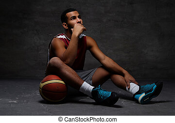 Pensive young African-American basketball player in sportswear sitting on a floor with a ball over dark background.