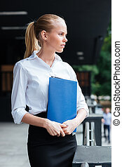 Pensive young business woman holding blue folder and looking away