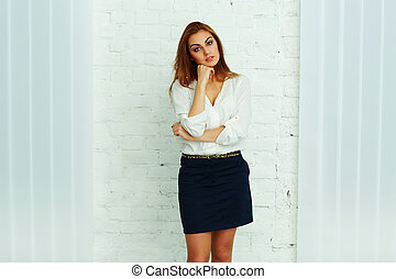 Pensive young businesswoman standing in office