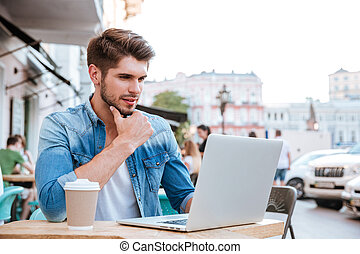 Pensive young casual man looking at laptop in cafe outdoors