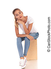 pensive young casual woman sitting on wooden box