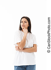 Pensive young casual woman standing