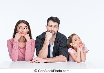 Pensive young family with one child looking at camera on white