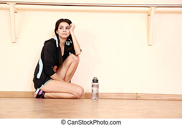 Pensive young fit woman leaning on the wall at gym