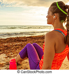 pensive young fit woman on seashore relaxing after workout