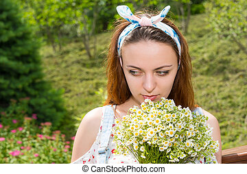 Pensive young girl smelling flowers