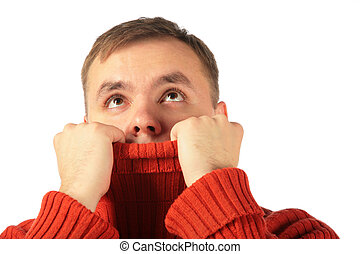 Pensive young man looks upward hiding in sweater