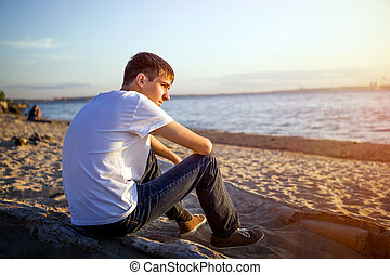 Pensive Young Man on the Seashore at the Sunset