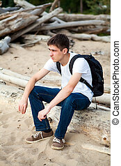 Pensive Young Man sit on the Log outdoor