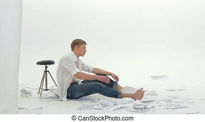Pensive Young Man Sitting On the Floor And Singing