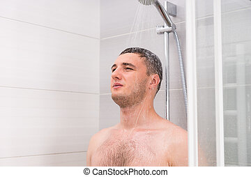 Pensive young man taking a shower in the bathroom