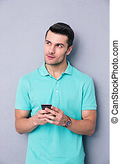 Pensive young man using smartphone