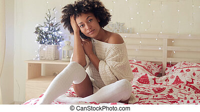 Pensive young woman celebrating Christmas alone sitting on...