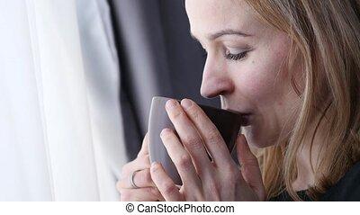 pensive young woman drinks coffee or tea near the window.