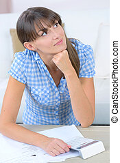 pensive young woman holding a calculator