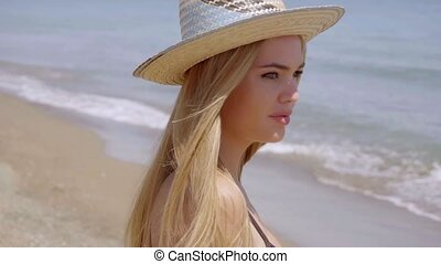Pensive young woman in a sunhat at the seaside standing...