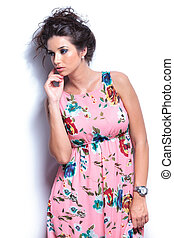 pensive young woman in floral dress looking away - side view...