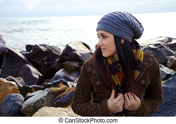 Pensive young woman in front of the ocean in the winter
