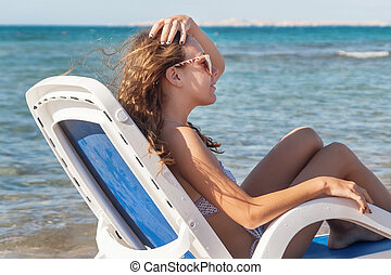 Pensive young woman in sunglasses is sitting in a deckchair, aga
