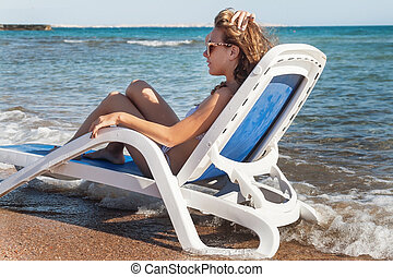 Pensive young woman in sunglasses is sitting in a deckchair, against the background of the sea and tropical beach with palm trees