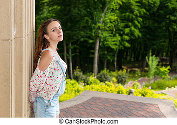 Pensive young woman standing near wall in a park