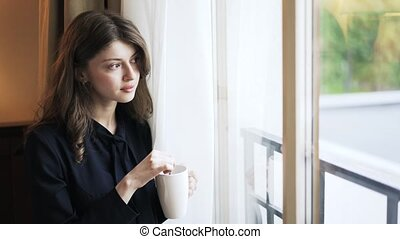 Pensive young woman with a cup looking through a window