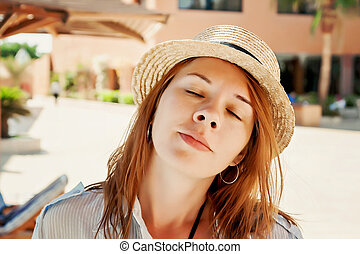 Pensive young woman with closed eyes in a straw hat, close-up portrait