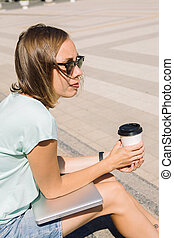 Pensive young woman with cup of coffee and laptop in the street