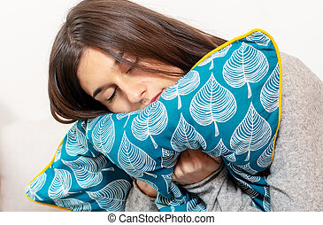 pensive young woman with pillow sitting on bed