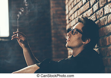 pensively smoke cigarette