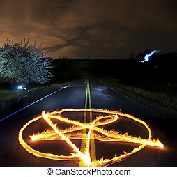 Pantagram made of fire flames in the middle of a country rural road at night time
