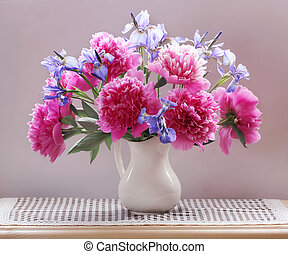 peonies and irises in a jug on the table.
