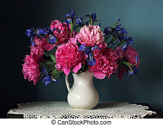 Peonies and irises in a white jug. Still life with flowers.