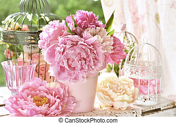 peony bunch in vase on the table in the garden with color...