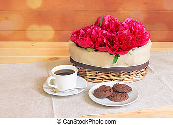 Peony flowers in wicker basket, cup of coffee and cookies on wooden table