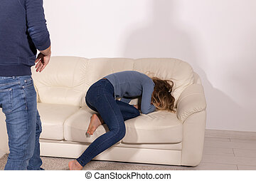 people, abuse and violence concept - aggressive man hitting his wife on sofa